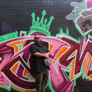 Artist Dawood Relm in front of Graffiti
