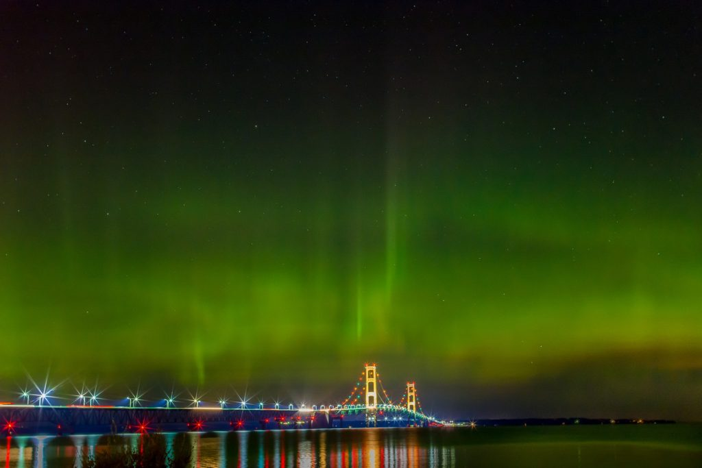 Mackinac bridge in michigan at night with northern lights above it