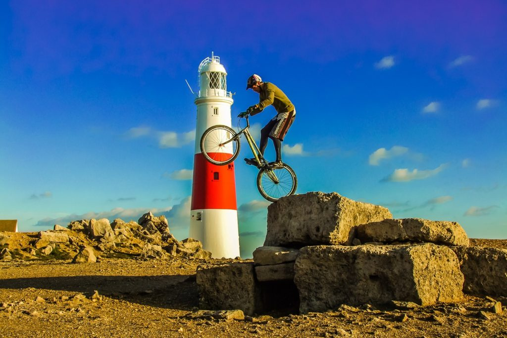 Portland, guy doing a trick on a bike in front of a lighthouse
