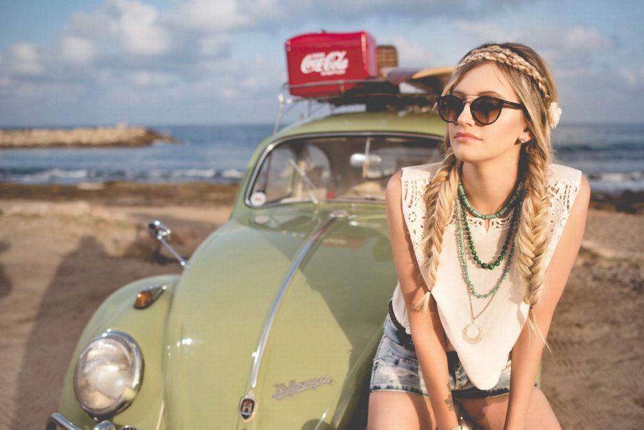 trendy girl sitting on car hood by the beach