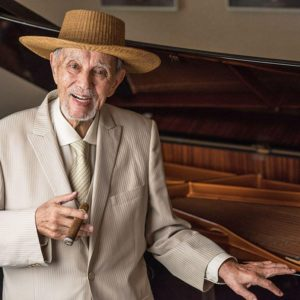 Avo Uvezian posing with cigar next to a piano