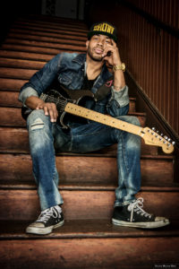 ayron jones posing with his guitar on the stairs