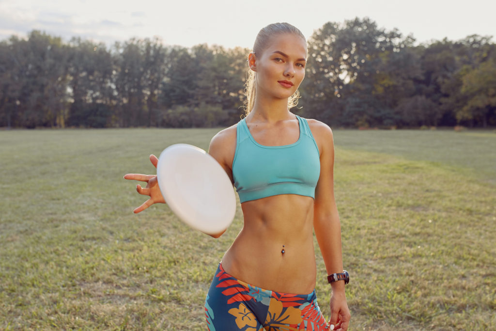 Attractive girl holding a frisbee