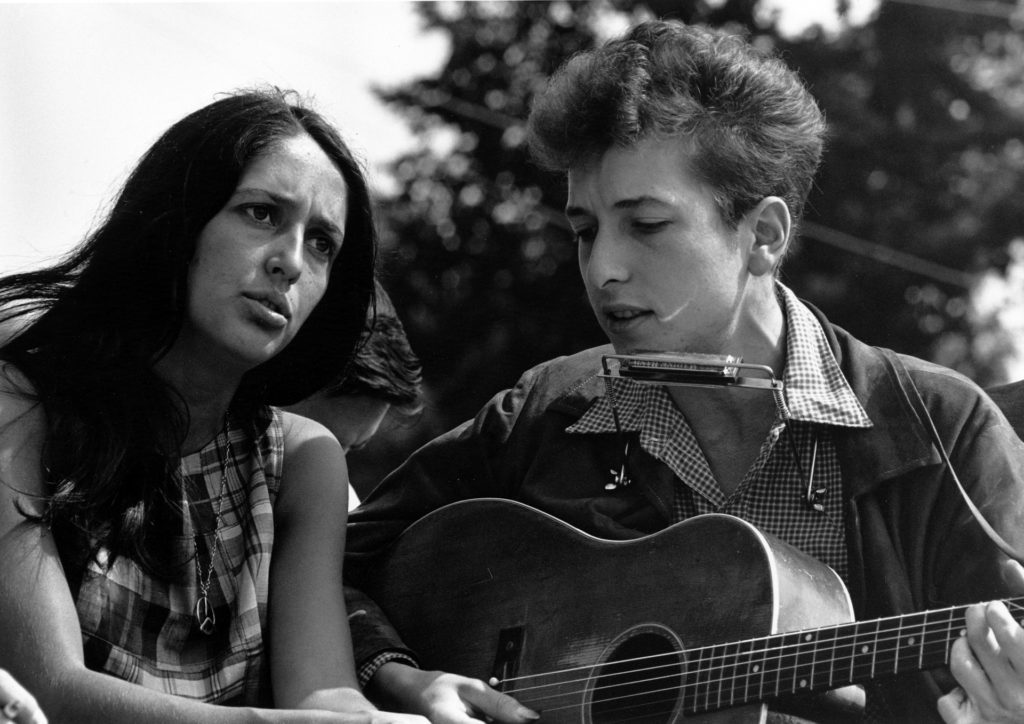 Bob Dylan plays a song next to Joan B