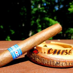cohiba blue cigar leaning on a Cuba ashtray outside