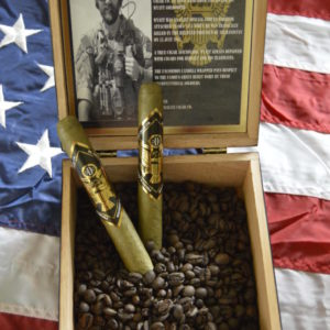 degenerate cigars gold star blend lying in coffee beans in a box on a flag