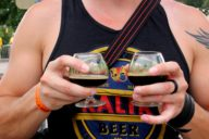 guy holds two beer glasses at beer camp