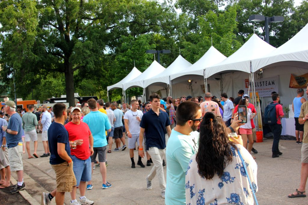 people mingle around tents at beer camp in Raleigh