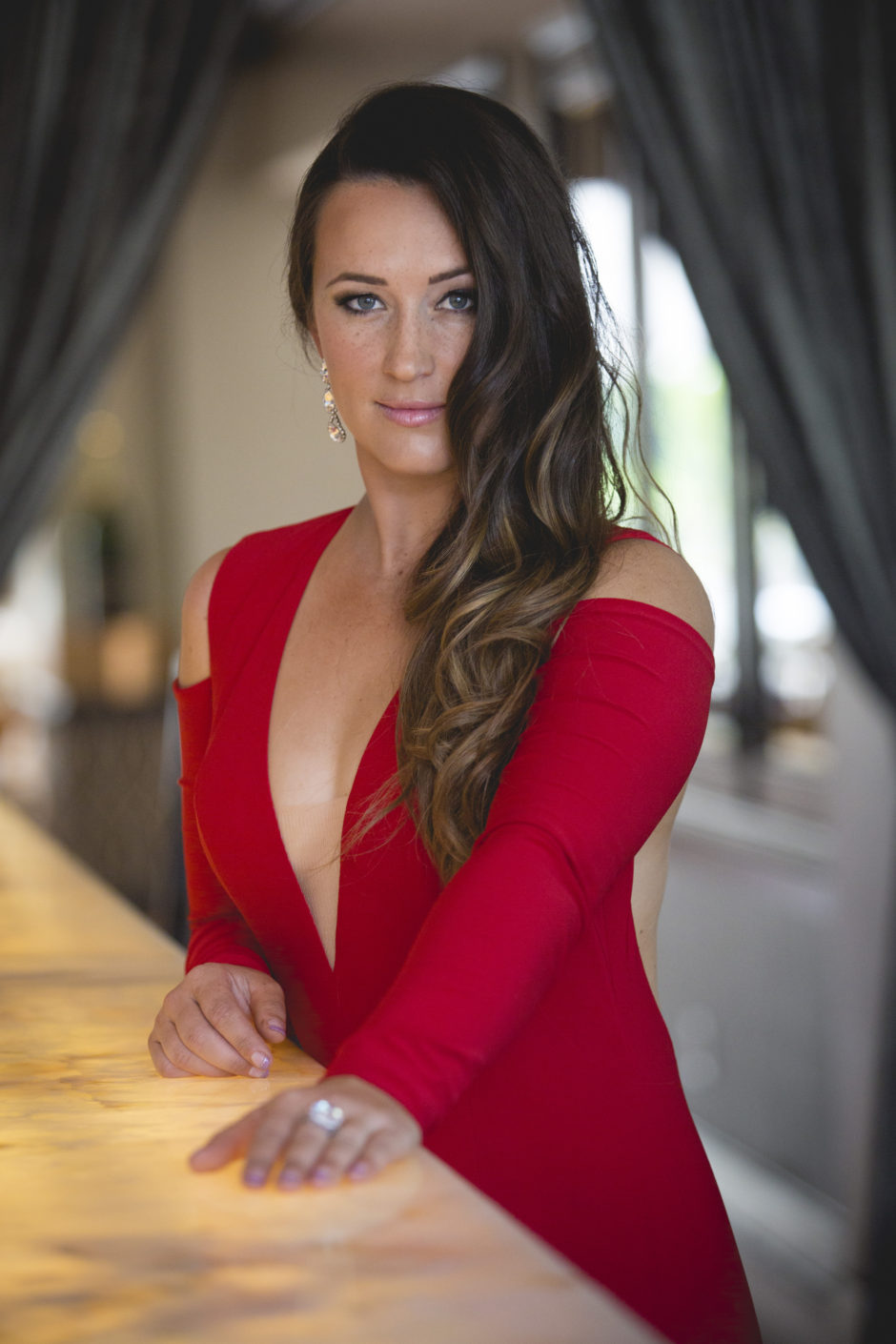Sara Price in a red dress standing at a bar