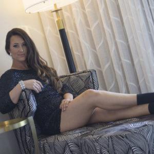 Sara Price lounging in a black dress