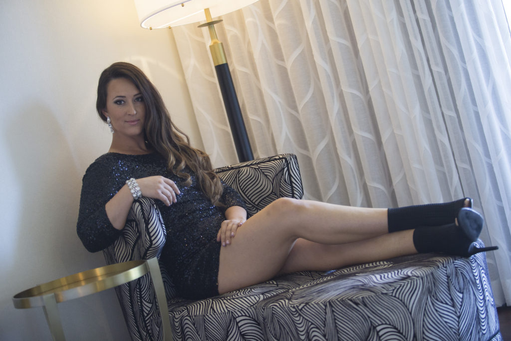 Sara Price lounging in a black dress