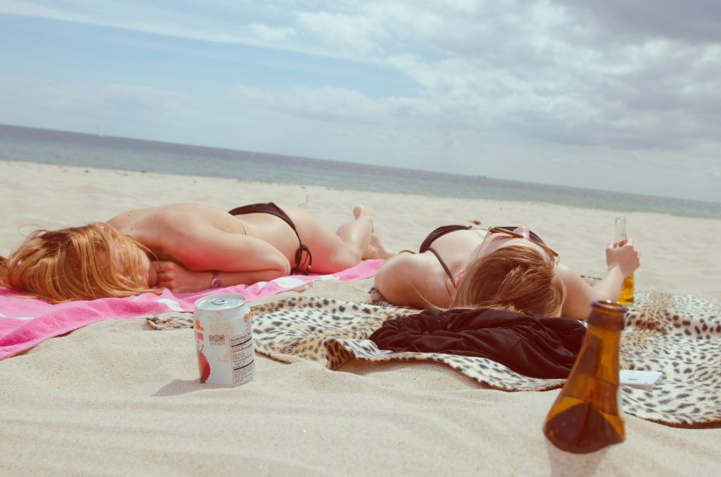 two girls laying on the beach with drinks