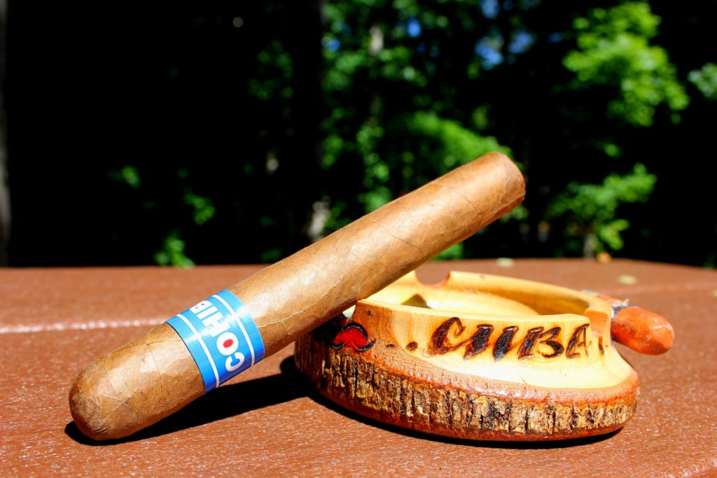 In Our humidor, cohiba blue cigar sitting on a Cuba ashtray outside