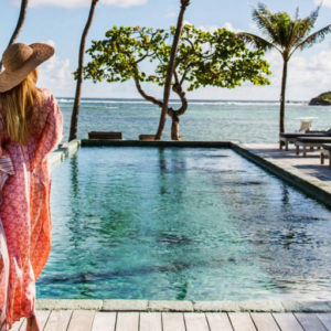 Girl stands by pool in St Barts overlooking ocean