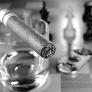 cigar on top of whiskey glass with cutter