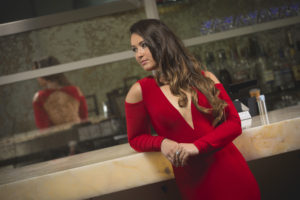 Sara Price in a red dress leaning against a bar