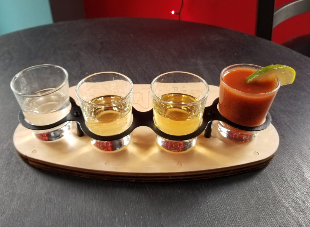 A tequila flight with (from left) a blanco, reposado, and añejo. The last glass is sangrita, a traditional, tomato-based drink that cleanses the palate.