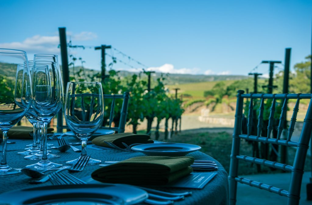 Vacations: Wine glasses set at a table overlooking a vineyard in California