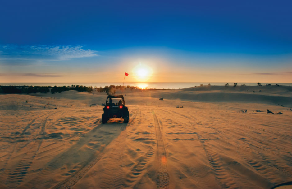 michigan what to do A dune buggy rides into the sunset at Silver Lakes Sand Dunes.
